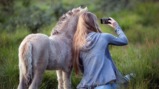 Девушка фотографируется с жеребёнком в осеннем поле