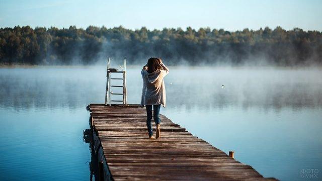 Девушка на деревянном пирсе у туманного озера ранней осенью