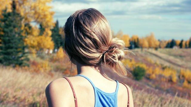Девушка с пучком на затылке в майке на тонких лямках в тёплый осенний день