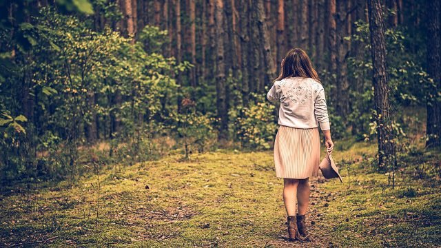 Девушка с шляпой в руках идёт в сторону осеннего леса