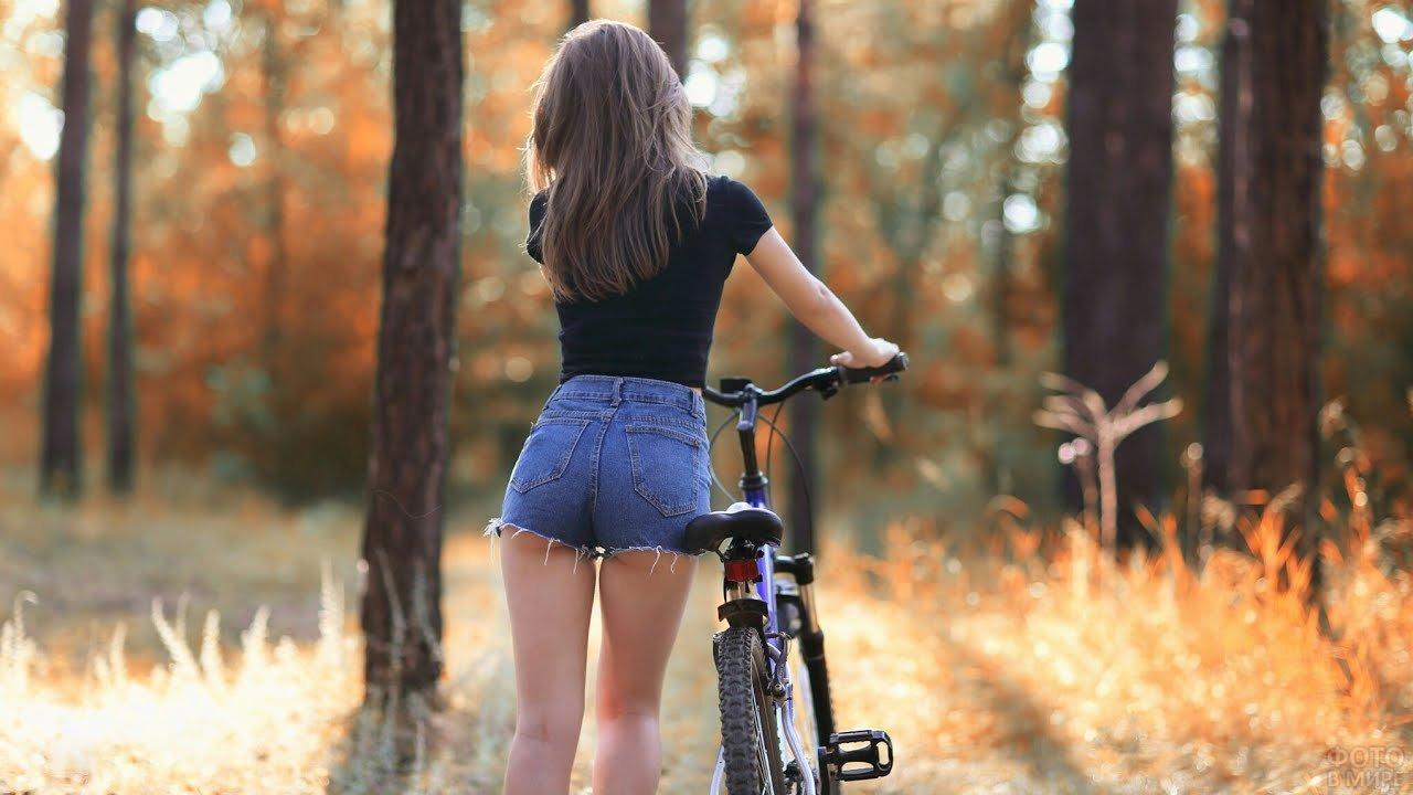 Девушка с велосипедом в парке