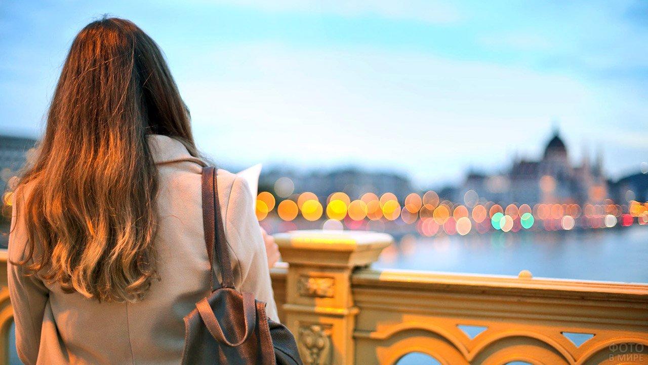 Девушка смотрит на вечерние огни осеннего Рима