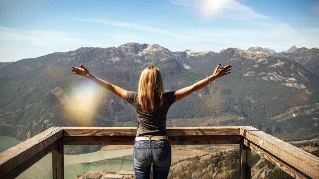 Девушка стоит раскинув руки на встречу солнцу ранней осенью в горах
