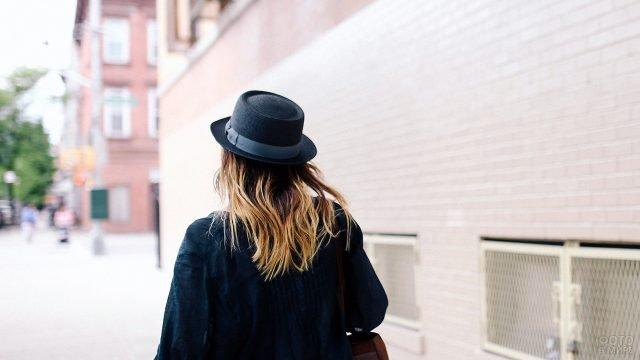 Девушка в чёрной шляпе идёт по осенней городской улице