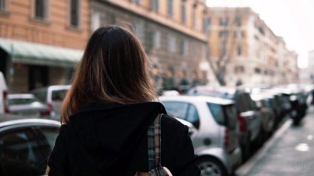 Девушка в чёрном пальто идёт вдоль парковки по осенней улице