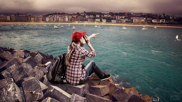 Девушка в красной кепке и клетчатой рубашке смотрит в бинокль на осенний залив с яхтами