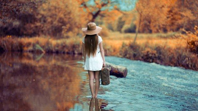 Девушка в шляпе стоит в речной воде на мелководье
