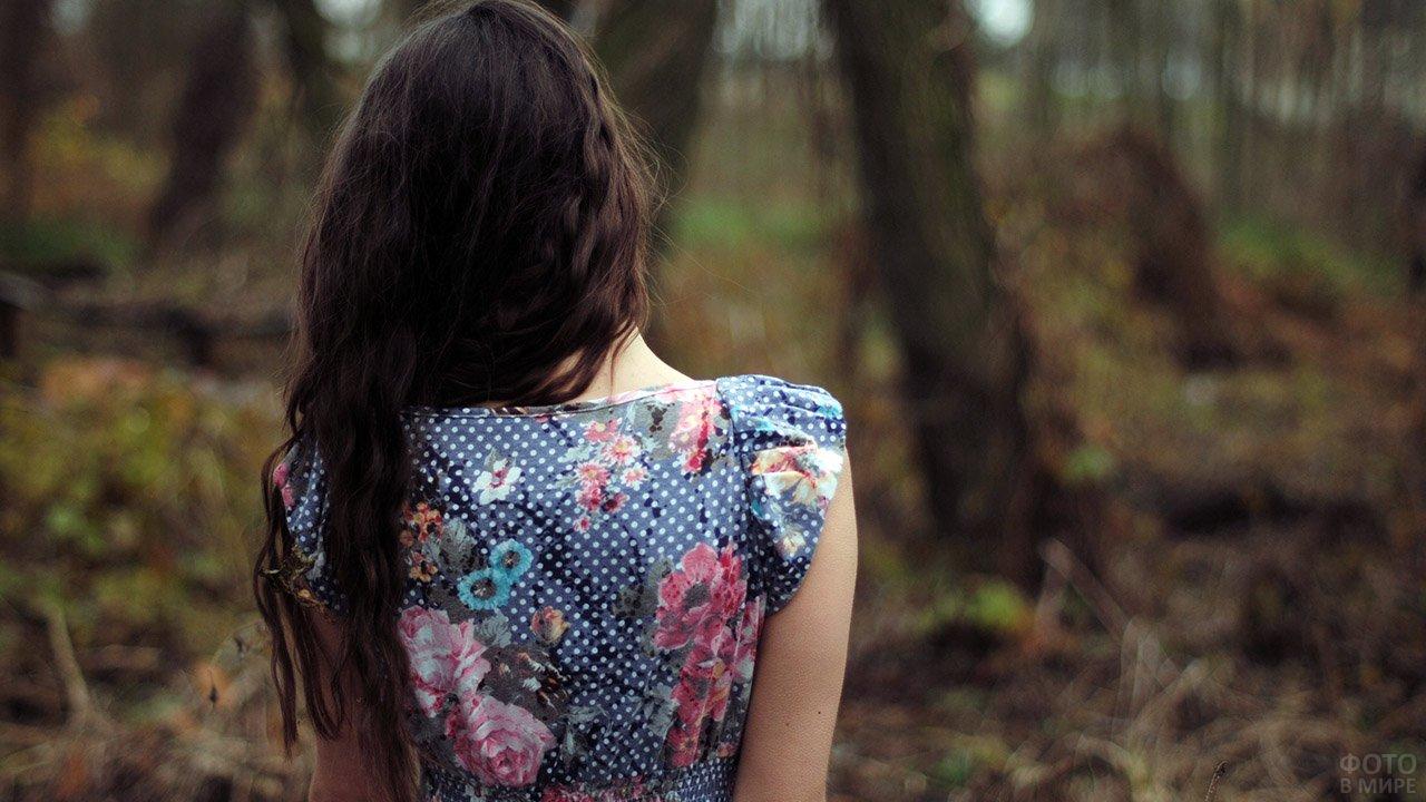 Длинноволосая брюнетка со спины в платье в цветочек в осеннем парке