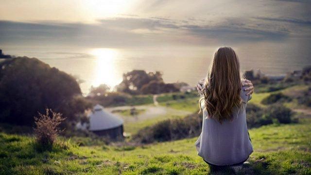 Длинноволосая девушка сидит обхватив плечи на осеннем холме у моря