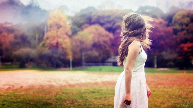 Длинноволосая девушка в белом платье на фоне красно-жёлтого осеннего парка