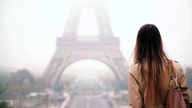 Длинноволосая девушка в плаще смотрит на Эйфелеву башню туманным осенним утром