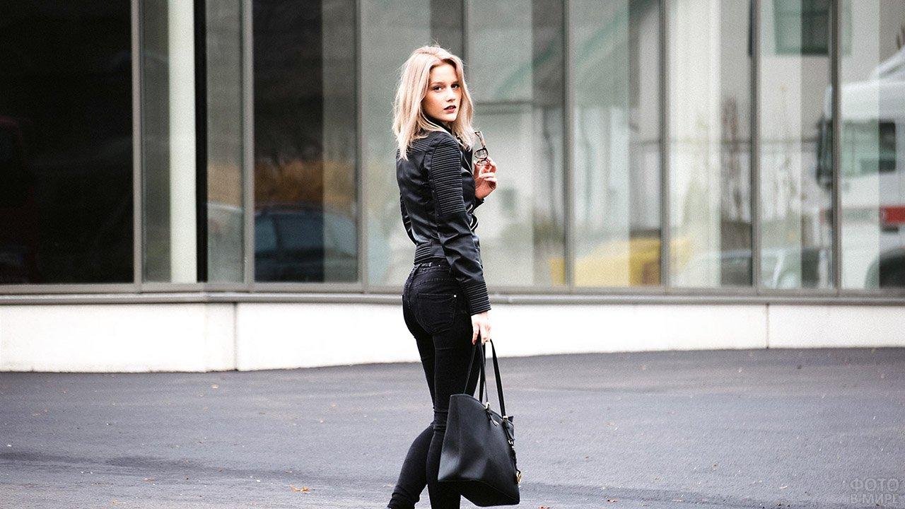 Фото блондинки в чёрном со спины на осенней улице