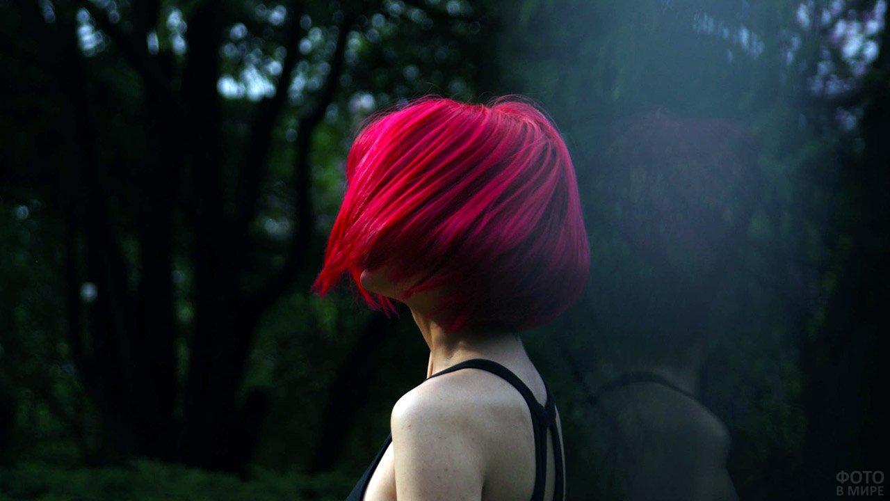 Красноволосая девушка со стрижкой каре смотрит на тёмный осенний парк