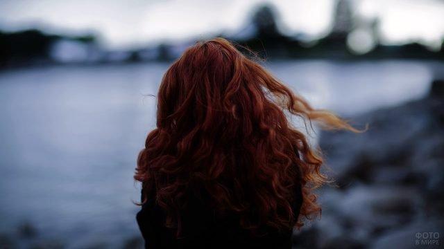 Рыжеволосая девушка со спины на фоне осеннего озера