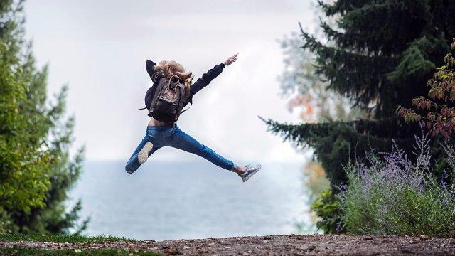 Счастливая туристка в прыжке у лесного озера ранней осенью