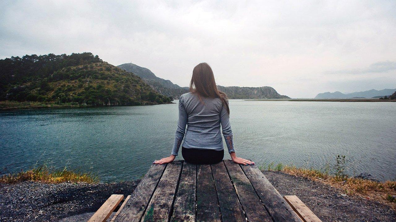Темноволосая девушка сидит на дощатом столе у осеннего горного озера