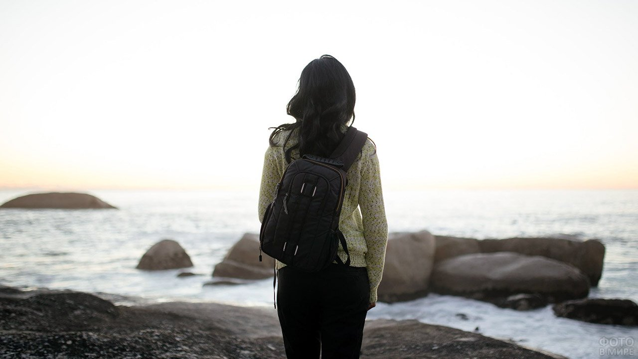 Туристка смотрит на осеннее море