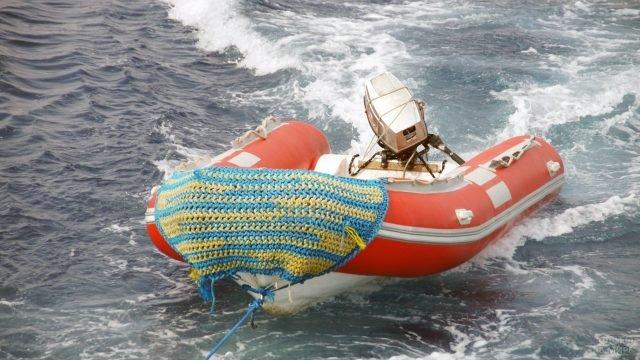 Красная надувная моторная лодка из ПВХ с жёстким дном на буксире