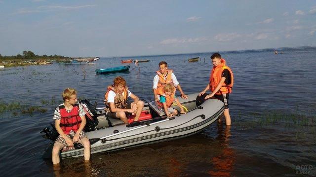 Мальчишки в надувной моторно-вёсельной лодке на мелководье Азовского моря