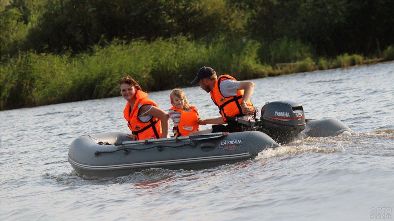 Молодая семья катается по реке в небольшой надувной моторно-гребной лодке из ПВХ