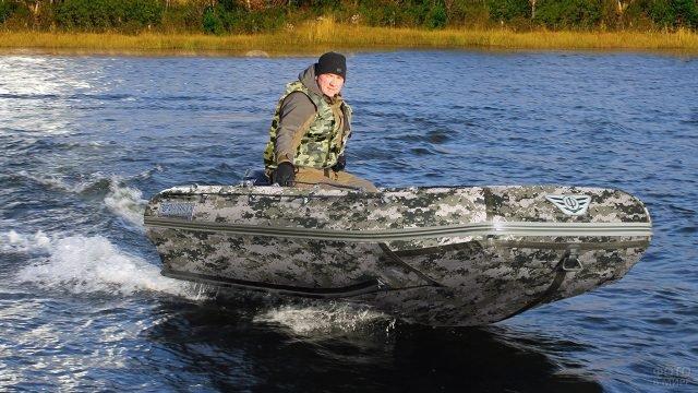 Мужчина в надувной лодке расцветки пиксельный камуфляж