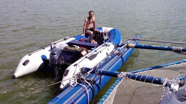 Мужчина в пришвартованной надувной моторно-вёсельной лодке из ПВХ