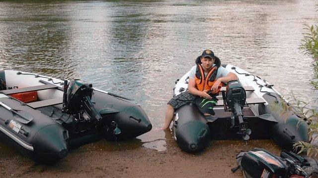 Мужчина в спасжилете позирует у двух моторно-гребных лодок из ПВХ