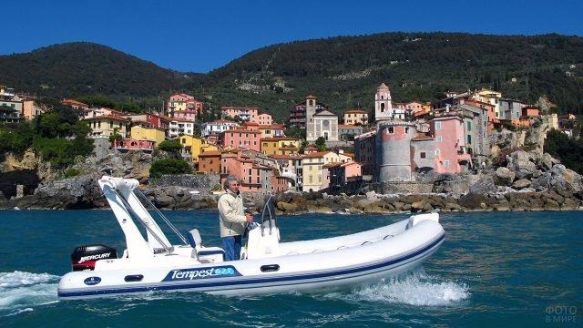 Мужчина за штурвалом моторной лодки для морских прогулок на фоне приморского европейского курорта