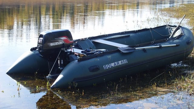 Надувная лодка из ПВХ с выключенным мотором на реке