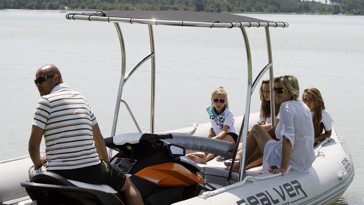 Семья туристов в белой надувной лодке из ПВХ с внутренним мотором