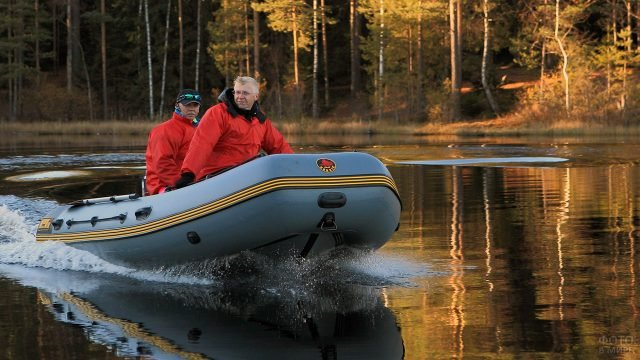 Туристы в красных куртках плывут на моторной надувной лодке
