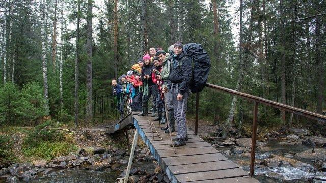 Группа туристов на мосту через реку Большая Тесьма в парке Таганай