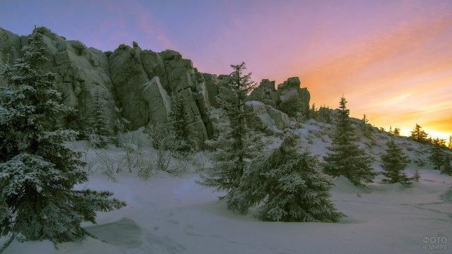 Отвесные скалы и заснеженные ели на фоне рассветного неба над парком Таганай