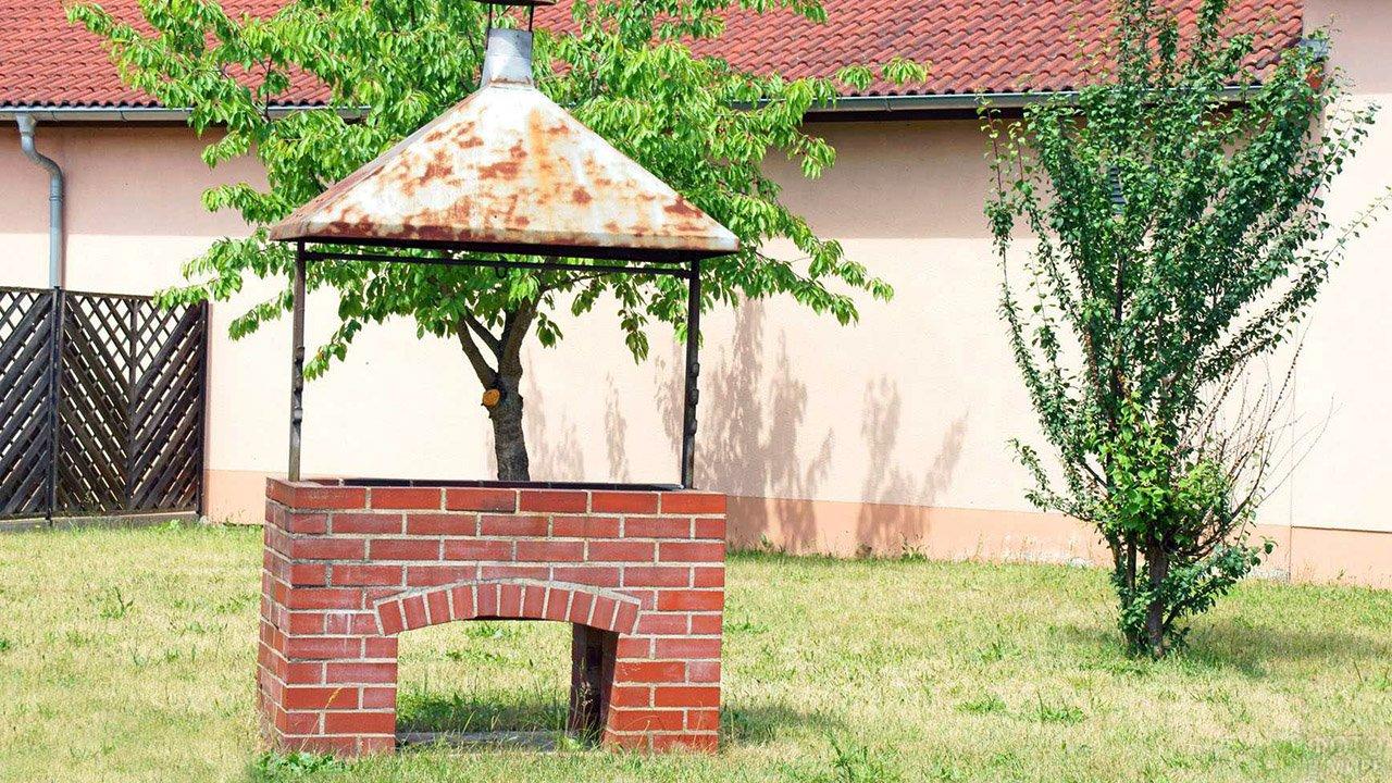 Мангал из кирпича с крышей на садовой лужайке