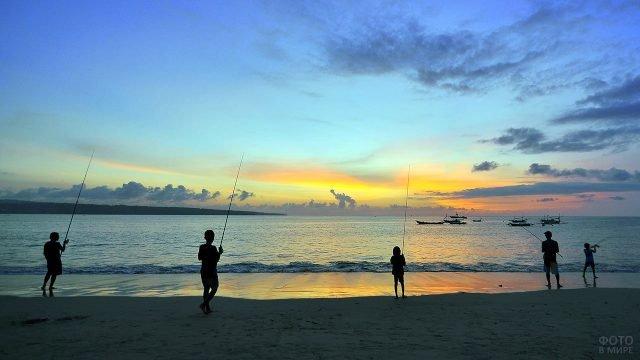 Дети с удочками на берегу вечернего тропического моря