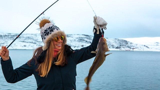 Девушка хвастается уловом на зимней рыбалке