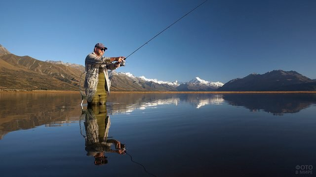 Довольный рыбак стоит с удочкой в воде горного озера
