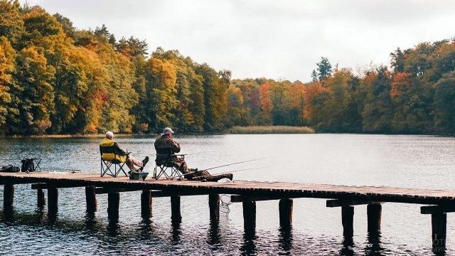 Двое рыбаков сидят на деревянном пирсе лесного осеннего озера