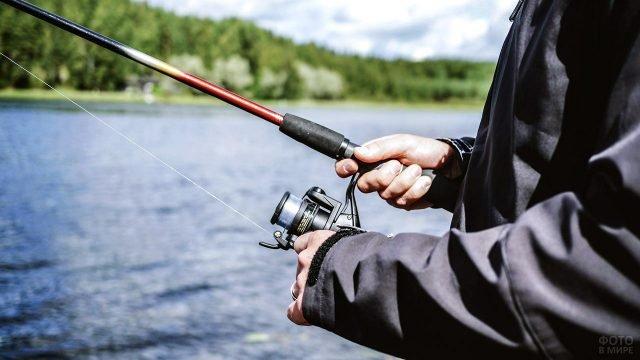 Мужчина держит спиннинг с катушкой крупным планом на фоне реки