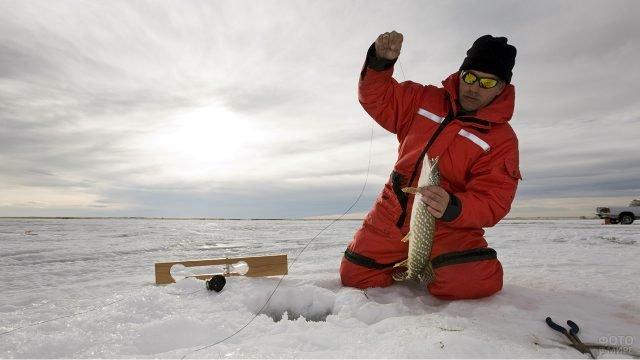 Мужчина с пойманной рыбой на фоне снежной равнины