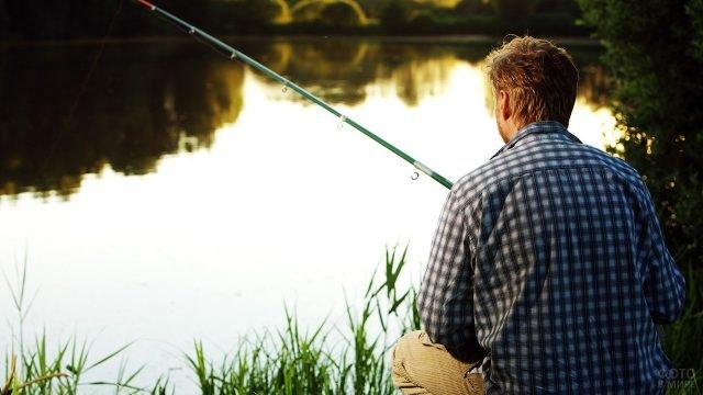 Мужчина с удочкой на вечернем берегу сельской реки