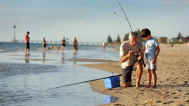 Мужчина с внуком на песчаном берегу разбираются с катушкой спиннинга