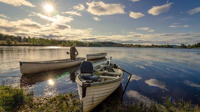 Мужчина снимает мотор с одной из трёх рыбацких лодок на фоне речного пейзажа