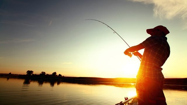 Мужчина со спиннингом на фоне утреннего солнца над берегом реки