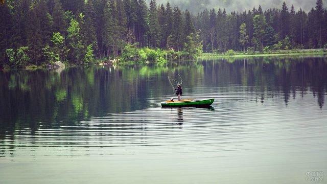 Мужчина закидывает спиннинг с лодки посреди лесного озера