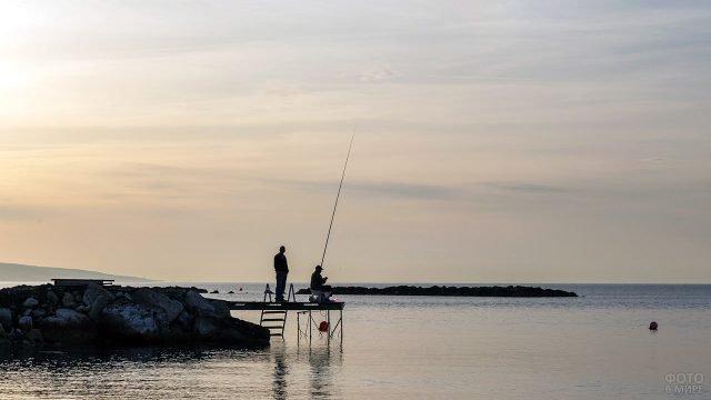 Мужчины на рассвете рыбачат с морского пирса