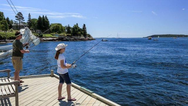 Отец с дочерью рыбачат с пирса на берегу озера