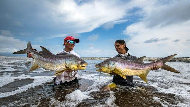 Отец с сыном позируют с уловом на морском мелководье