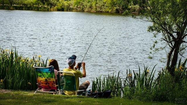 Парочка в складных шезлонгах рыбачит на берегу летнего озера