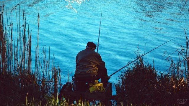 Пенсионер рыбачит на берегу ярко-синей речки